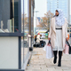 Young stylish Arabic woman in hijab dreamily walking around street with shopping bags - PhotoDune Item for Sale