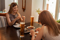 Two girl friends have coffee and dessert in modern restaurant - PhotoDune Item for Sale