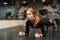 Attractive young woman does plank exercise in gym - PhotoDune Item for Sale