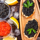 Top view of black surgeon and red salmon caviar on wooden table - PhotoDune Item for Sale