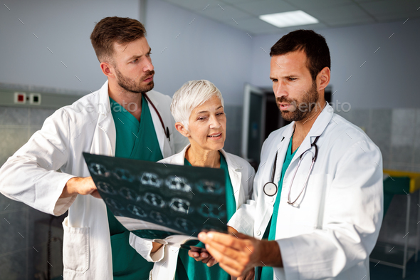 Doctors examining an x-ray report in hospital to make diagnosis - Stock Photo - Images