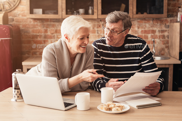 Happy Senior Couple Planning Family Budget Together With Laptop And Papers - Stock Photo - Images