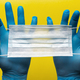 Doctor Holds Antivirus Face Mask in Hands in Blue Medical Gloves on Yellow Background - PhotoDune Item for Sale