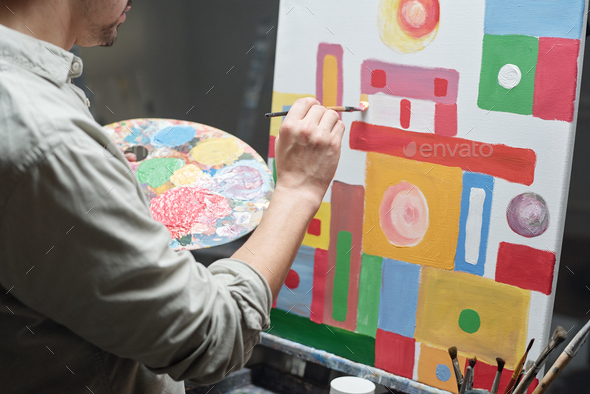 Young male artist with color palette and paintbrush working over painting - Stock Photo - Images