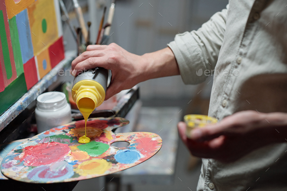Hand of young painter adding yellow color on palette before start painting - Stock Photo - Images