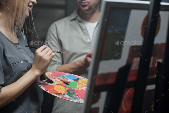 Teacher of painting consulting his student with paintbrush and color palette - Stock Photo - Images