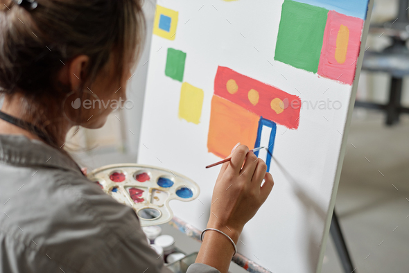 Hand of young female artist holding color palette while painting picture - Stock Photo - Images