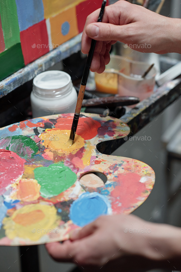 Hand of young professional painter mixing colors on palette in front of easel - Stock Photo - Images