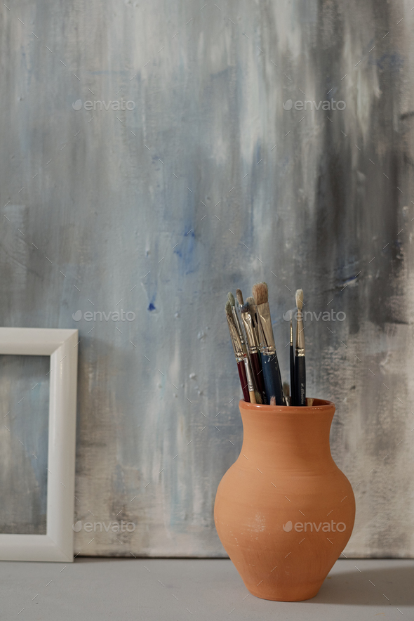 Brown clay jug with group of paintbrushes standing on the floor against painting - Stock Photo - Images
