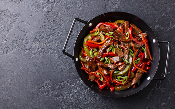 Beef and Vegetables Stir Fry in a Pan. Dark Background. Copy Space. Top view. - Stock Photo - Images