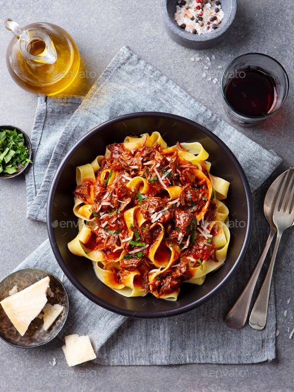 Pasta Pappardelle with Beef Ragout Sauce in Black bowl. Grey Background. Top view. - Stock Photo - Images