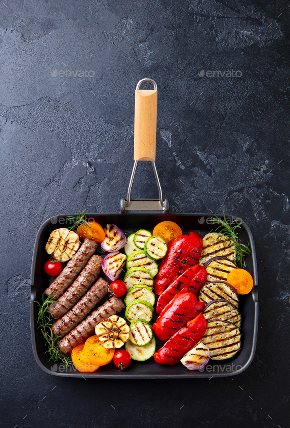 Grilled Meat Kebab and Vegetables in Grill Pan. Black Stone Background. Top view. - Stock Photo - Images