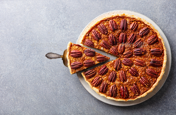 Pecan nut pie, on a plate. Grey background. Copy space. Top view. - Stock Photo - Images