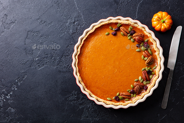 Pumpkin pie in baking dish. Black slate background. Copy space. Top view. - Stock Photo - Images