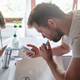 Young caucasian man in bathroom brushing his teeth while texting on mobile phone - PhotoDune Item for Sale