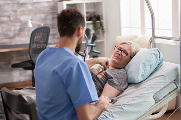 Old woman in nursing home looking at male doctor - Stock Photo - Images