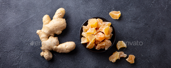 Candied ginger in black bowl on dark stone background. Top view. Copy space. - Stock Photo - Images