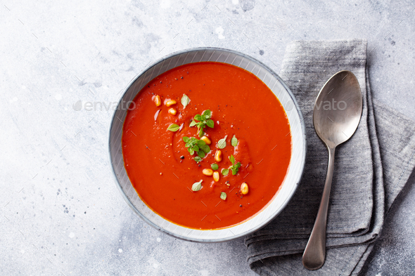 Tomato soup with fresh herbs and pine nuts in a bowl. Grey stone background. Top view. - Stock Photo - Images