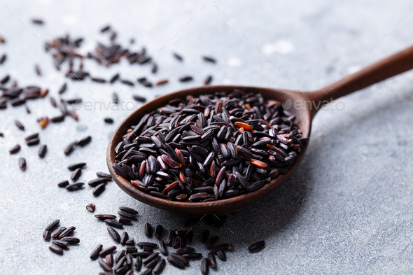 Black wild rice in a wooden spoon. Grey stone background. Close up. - Stock Photo - Images