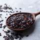 Black wild rice in a wooden spoon. Grey stone background. Close up. - PhotoDune Item for Sale