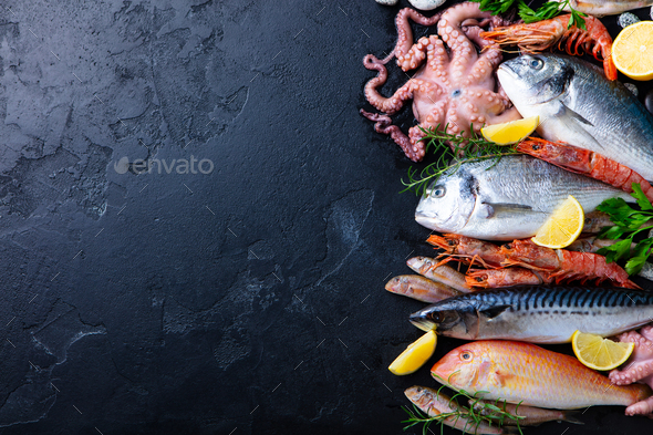 Fresh Raw Fish and Seafood Assortment on Black slate Background. Top View. Copy Space. - Stock Photo - Images