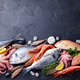 Fresh fish and seafood assortment on black slate background. Copy space. Top view. - PhotoDune Item for Sale