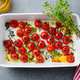 Roasted cherry tomatoes with herbs in baking dish. Grey background. Top view. - PhotoDune Item for Sale