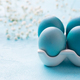 Easter Eggs in a Porcelain Egg Box with White Flowers on a Blue Background. Close up. - PhotoDune Item for Sale