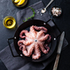 Octopus in a black frying pan. Black stone background. Top view. - PhotoDune Item for Sale