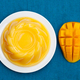 Mango pudding, jelly, dessert on white plate. Blue textile background. Top view. - PhotoDune Item for Sale