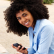Close up attractive young african american girl relaxing outside with smart phone - PhotoDune Item for Sale