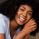 Close up cheerful african american woman lying on floor in living room and laughing - PhotoDune Item for Sale