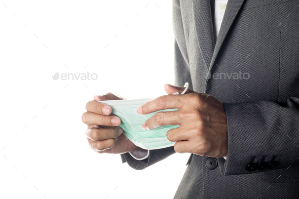 Man in gray suit holding face mask - Stock Photo - Images