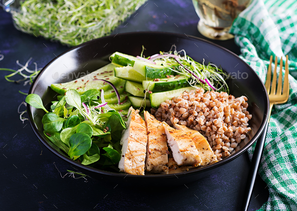 Buddha bowl with buckwheat porridge, grilled chicken fillet, corn salad, microgreens - Stock Photo - Images