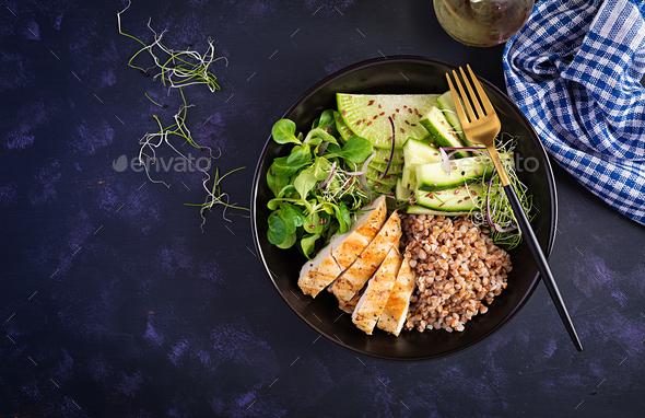 Buddha bowl with buckwheat porridge, grilled chicken fillet, corn salad, microgreens and daikon - Stock Photo - Images