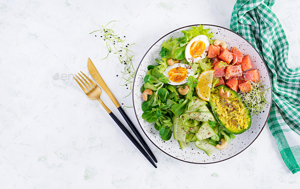 Salt salmon salad with greens, cucumbers, eggs and avocado - Stock Photo - Images
