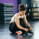 Athletic woman tying her sneakers at the gym - PhotoDune Item for Sale