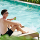Pensive man sitting by swimming pool - PhotoDune Item for Sale
