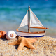 Toy ship and seashells on sand near sea. Summer vacation concept - PhotoDune Item for Sale