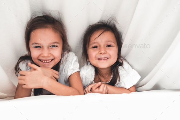 two girls reading under blanket - Stock Photo - Images