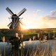 golden sunshine behind windmill by river - PhotoDune Item for Sale