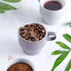Ceramic cups with freshly roasted coffee beans and fresh ground aromatic coffee on a light - PhotoDune Item for Sale