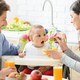 Young mother and father feeding baby son at kitchen - PhotoDune Item for Sale