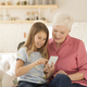 Mature woman playing video games on smartphone with her granddaughter at home - PhotoDune Item for Sale