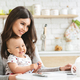 Young mom typing on laptop, sitting with baby at kitchen - PhotoDune Item for Sale