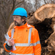 Forestry technician posing with clipboard notepad next to tree log - PhotoDune Item for Sale