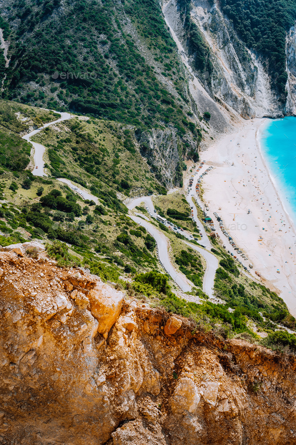 Serpentine zigzag road down to famous Myrtos Beach. Orange rocks ravine on side. Sunny beach from - Stock Photo - Images
