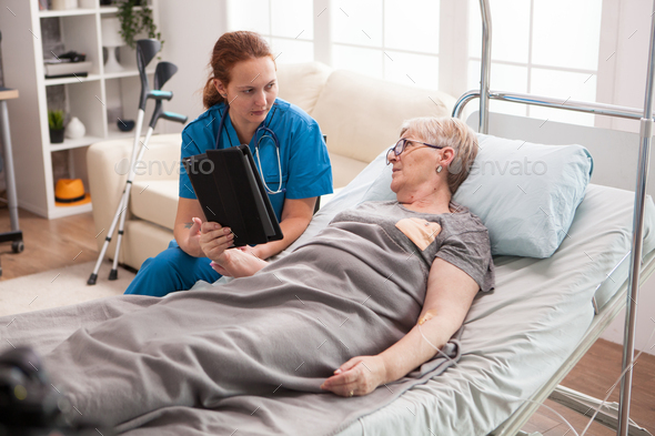 Female doctor in nursing home using tablet computer - Stock Photo - Images