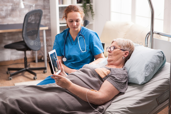 Old woman in nursing home sitting in bed using tablet computer - Stock Photo - Images