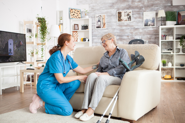 Cheerful old woman sitting on couch in a a nursing home - Stock Photo - Images
